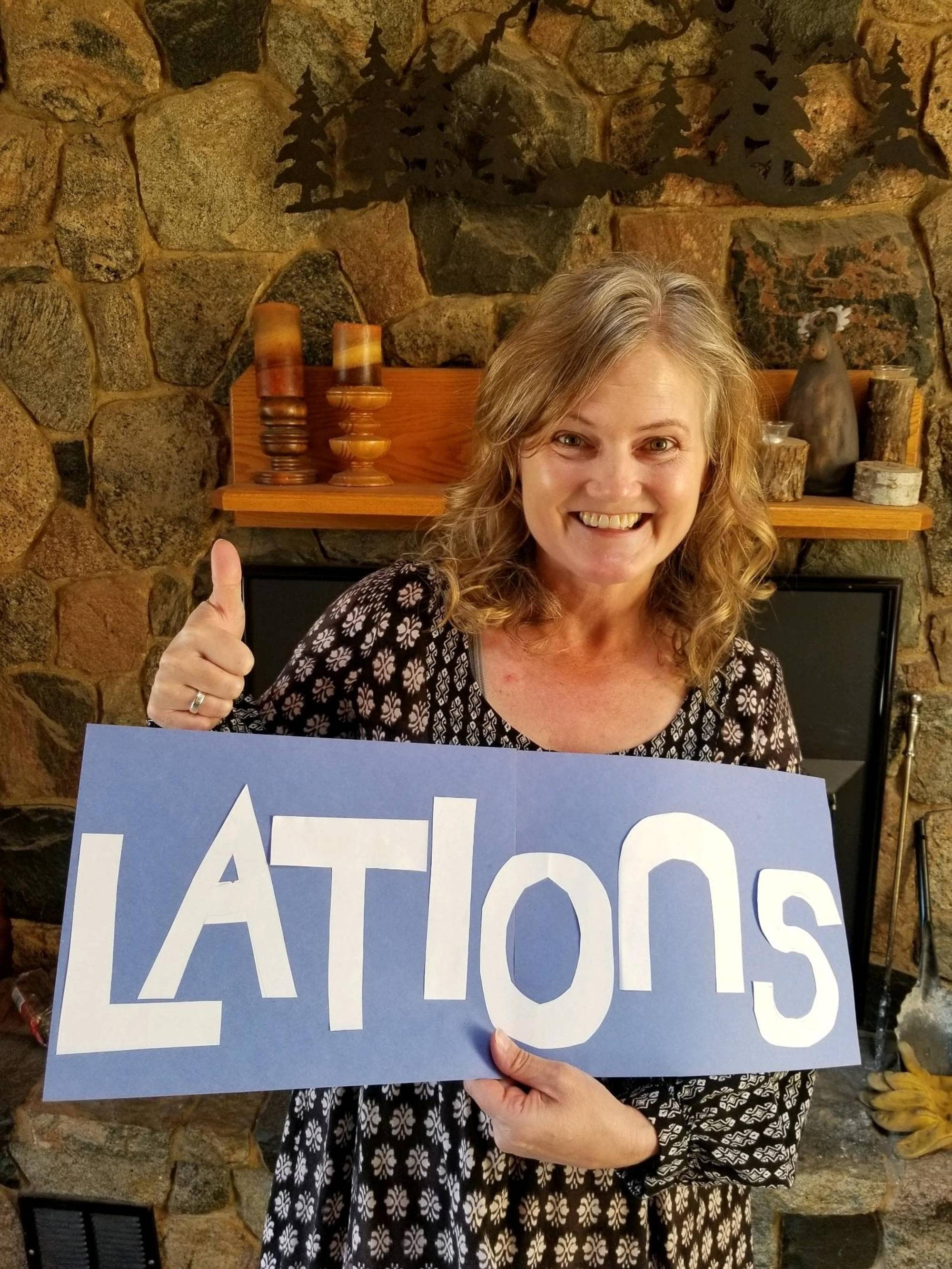 "Faculty holding sign with the word ""lations"""